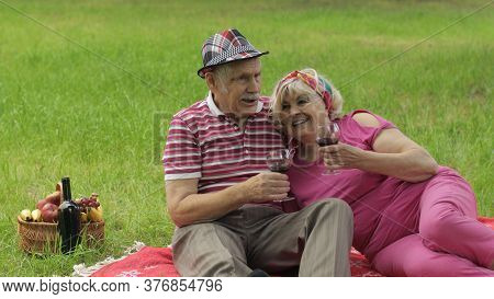 Family Weekend Picnic In Park. Old People, Active Senior Caucasian Couple Sit On Blanket And Drink W
