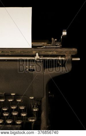 An Antique Typewriter With A Blank Piece Of Paper.