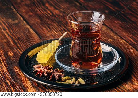 Oriental Glass With Tea And Navad On Metal Tray Over Wooden Surface
