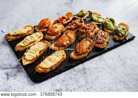 Assorted Bruschetta With Various Toppings On A Dark Plate On White Background. Appetizing Bruschetta