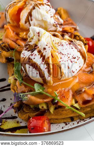 Closeup On Salmon Waffle With Poached Egg Cheese And Condiments