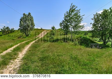 Beautiful Panorama Of A Meadow With A Dirt Road Going Up The Hill And A Wooden Table With Benches In