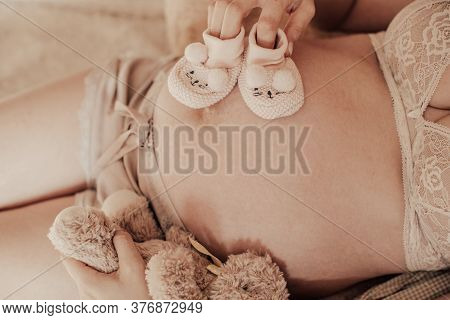 Pregnant Happy Woman Holding Baby Shoes In Her Hands. Mom Expecting Baby. Pregnant Belly. Pregnancy.