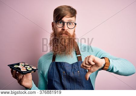 Redhead Irish cook man with beard holding maki sushi tray over isolated background with angry face, negative sign showing dislike with thumbs down, rejection concept