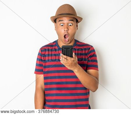 Asian Men Are Using Smartphones. He Looks At The Phone Then Made A Very Surprised Face. He Is Around