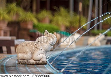 Luxury Outdoor Pool And Elephant Water. Elephant Statues Spray Water From A Swimming Pool. Elephant