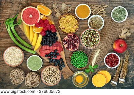 Super food for health and fitness with foods high in antioxidants, anthocyanins, vitamins, minerals, protein,  smart carbs, omega 3 &  fibre. Immune boosting. Flat lay on rustic wood background.