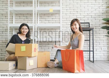 Merchant Two Attractive Young Asian Women Make Living Selling Products Online. They Are Checking The