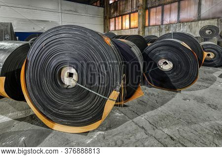 Rubber Conveyor Belt Factory. Black Large Massive Rolls Of Tape Are Prepared For Transportation. Fin
