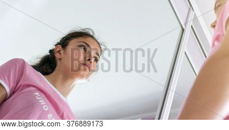 Young Woman In Purple T-shirt Looks At Reflection In Mirror Standing In Bathroom At Home In Early Mo