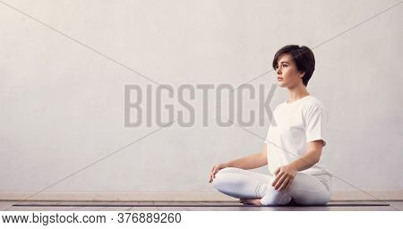 Young and fit woman practicing yoga indoor in the class. Stretching exercise in the day light. Sport, fitness, health care and lifestyle.