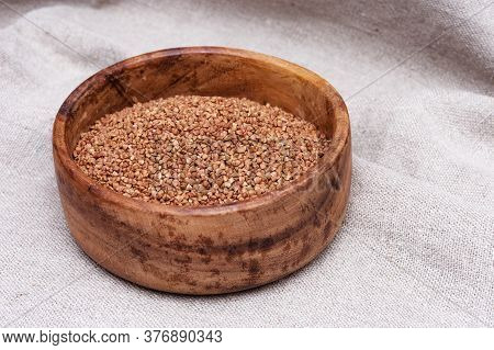Buckwheats In Round Rustic Bowl On Sackcloth Surface. Healthy Food Background. Organic Healthy Diet