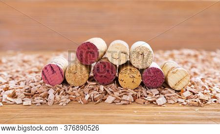 Corks With Red Stain Lie In A Stack On Background From Wood Chips. Natural Wood Fon With Heap Of Cor