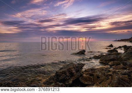 Dramatic Sunset Over Beach With A Natural Pond In The Foreground.