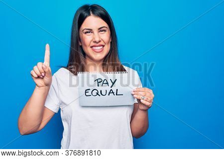 Young beautiful woman asking for gender equality holding paper with pay equal message smiling with an idea or question pointing finger with happy face, number one