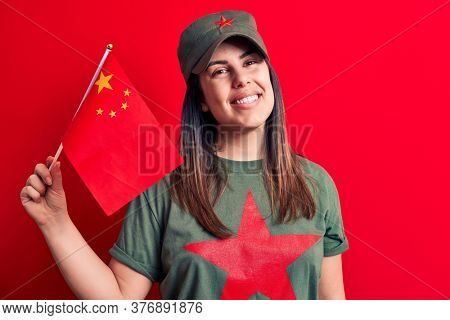 Beautiful patriotic woman wearing t-shirt with red star communist symbol holding china flag looking positive and happy standing and smiling with a confident smile showing teeth
