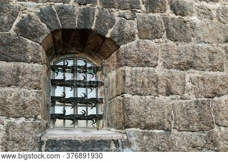 Window With Wrought Iron Grille On Dark Stone Wall. Wall Of Old House. Building Facade.