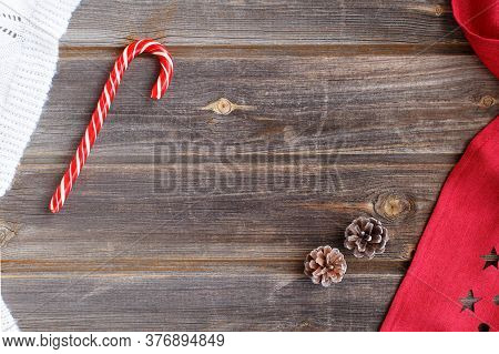 New Year Flat Lay: Christmas Candy Cane, Tiny Cones, White Woolen Plaid And Red Tablecloth With Star