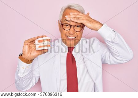 Middle age senior grey-haired dentist man holding prosthesis denture over pink background stressed with hand on head, shocked with shame and surprise face, angry and frustrated. Fear and upset