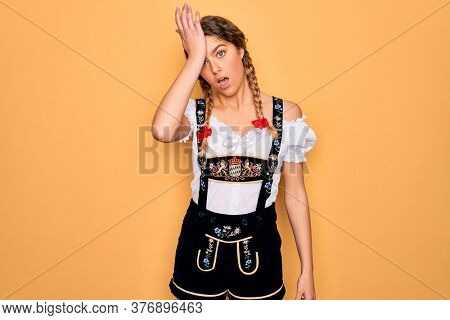 Young beautiful blonde german woman with blue eyes wearing traditional octoberfest dress surprised with hand on head for mistake, remember error. Forgot, bad memory concept.