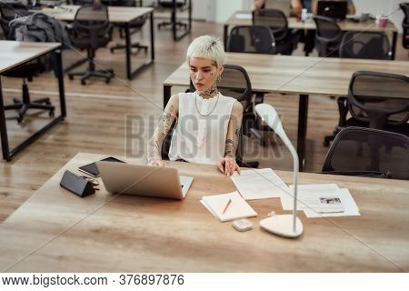 Young Busy Tattooed Business Woman With Short Haircut Working On Her Laptop While Sitting In The Off