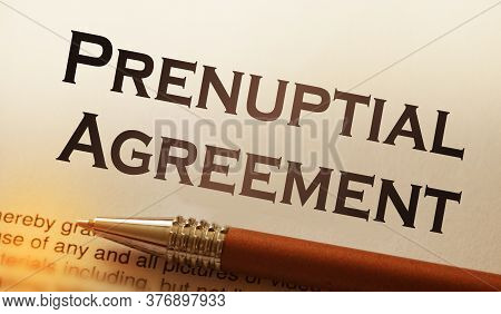 A Pen On Paper With Words Prenuptial Agreement. Marriage Contract Concept