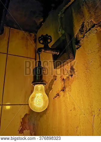 An Incandescent Light Bulb On An Unusual Sconce In The Form Of A Water Tap In A Dark Room. Interior