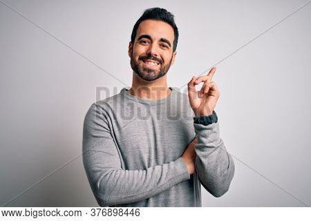 Young handsome man with beard wearing casual sweater standing over white background with a big smile on face, pointing with hand and finger to the side looking at the camera.