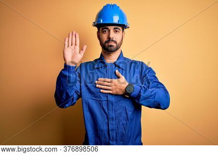 Mechanic man with beard wearing blue uniform and safety helmet over yellow background Swearing with hand on chest and open palm, making a loyalty promise oath
