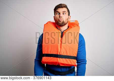 Young blond tourist man with beard and blue eyes wearing lifejacket over white background making fish face with lips, crazy and comical gesture. Funny expression.