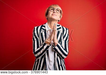 Blonde business woman with short hair wearing glasses and striped jacket over red background begging and praying with hands together with hope expression on face very emotional and worried. Begging.
