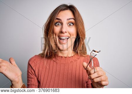 Young beautiful brunette woman using eyelash curler over isolated white background very happy and excited, winner expression celebrating victory screaming with big smile and raised hands