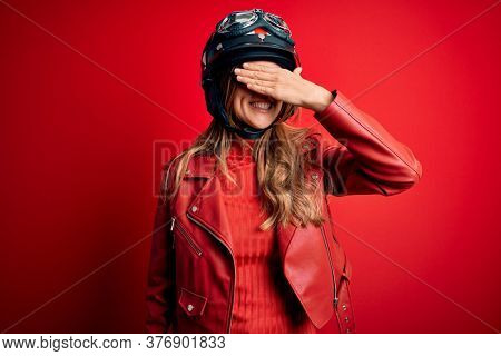 Young beautiful brunette motrocyclist woman wearing moto helmet over red background smiling and laughing with hand on face covering eyes for surprise. Blind concept.