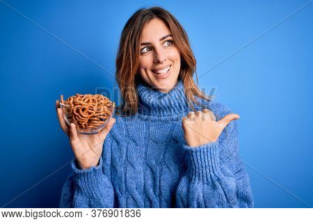 Young beautiful brunette woman holding bowl german baked pretzels over blue background pointing and showing with thumb up to the side with happy face smiling