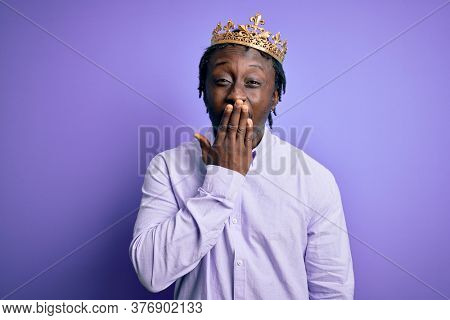 Young african american man wearing golden crown of king over isolated purple background bored yawning tired covering mouth with hand. Restless and sleepiness.