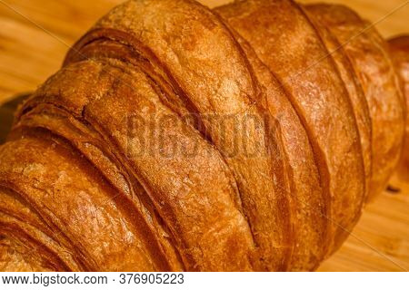 Detail Of Fresh Croissant On Wooden Table. Food And Breakfast Concept. Close Up Photo Of French Butt