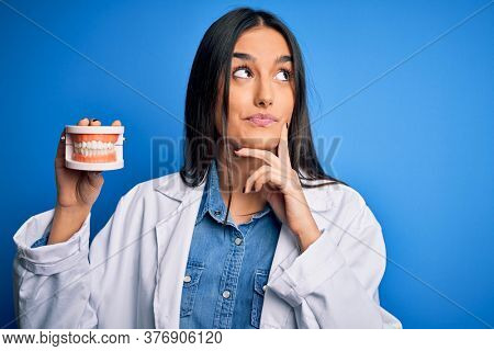 Young beautiful brunette dentist woman wearing coat holding plastic teeth prosthesis serious face thinking about question, very confused idea