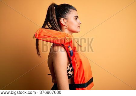 Young beautiful brunette woman wearing orange safe lifejacket over yellow background looking to side, relax profile pose with natural face with confident smile.
