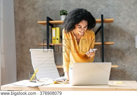 Attractive African American Business Woman Is Using Mobile Phone While Standing In A Modern Office L