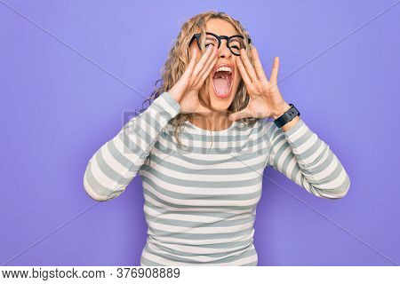 Beautiful blonde woman wearing casual striped t-shirt and glasses over purple background Shouting angry out loud with hands over mouth