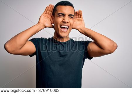 Young handsome african american man wearing casual t-shirt standing over white background Trying to hear both hands on ear gesture, curious for gossip. Hearing problem, deaf
