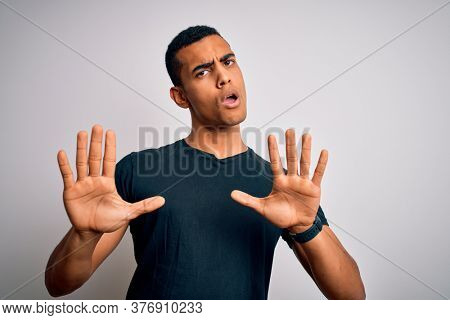 Young handsome african american man wearing casual t-shirt standing over white background Moving away hands palms showing refusal and denial with afraid and disgusting expression. Stop and forbidden.