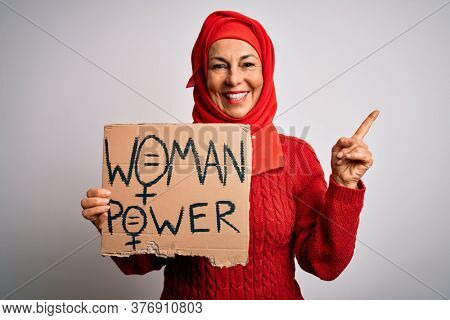 Middle age woman wearing muslim hijab asking for women rights holding banner very happy pointing with hand and finger to the side