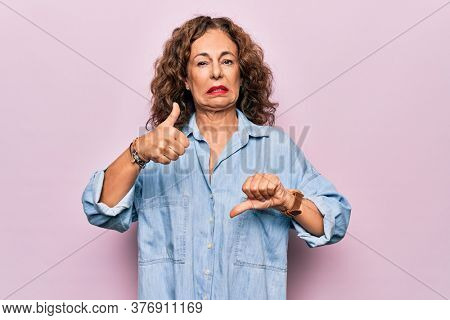 Middle age beautiful woman wearing casual denim shirt standing over pink background Doing thumbs up and down, disagreement and agreement expression. Crazy conflict