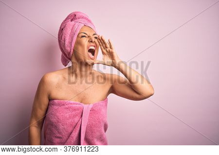 Middle age woman wearing bath towel from beauty body care over pink background shouting and screaming loud to side with hand on mouth. Communication concept.
