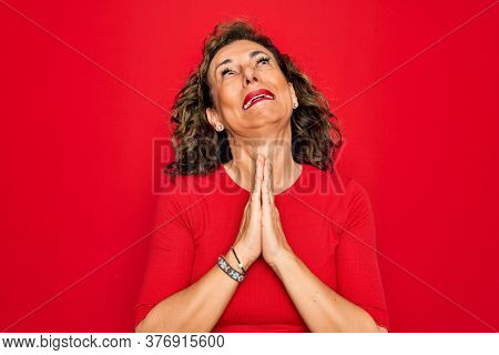 Middle age senior brunette woman wearing casual t-shirt standing over red background begging and praying with hands together with hope expression on face very emotional and worried. Begging.