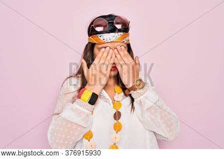 Young hispanic hippie woman wearing fashion boho style and sunglasses over pink background rubbing eyes for fatigue and headache, sleepy and tired expression. Vision problem