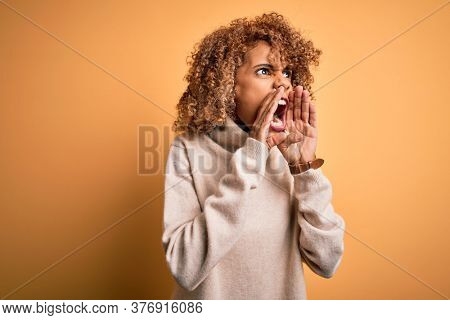 Young beautiful african american woman wearing turtleneck sweater over yellow background Shouting angry out loud with hands over mouth
