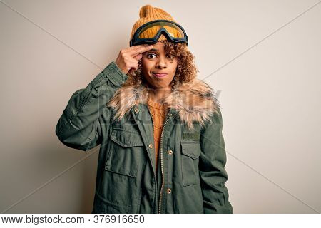 Young african american skier woman with curly hair wearing snow sportswear and ski goggles worried and stressed about a problem with hand on forehead, nervous and anxious for crisis
