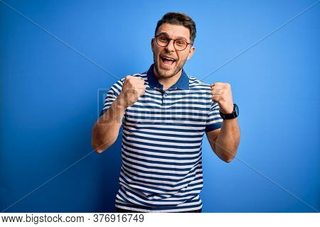 Young man with blue eyes wearing glasses and casual striped t-shirt over blue background celebrating surprised and amazed for success with arms raised and open eyes. Winner concept.